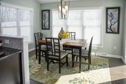Hardwood flooring from the kitchen extends into the sunroom. The sunroom is decorated as a dining area.