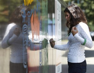 Kristen Carbone, executive director of Tape Art and a Buffalo native, works on a section of the wall.   (Sharon Cantillon /Buffalo News)