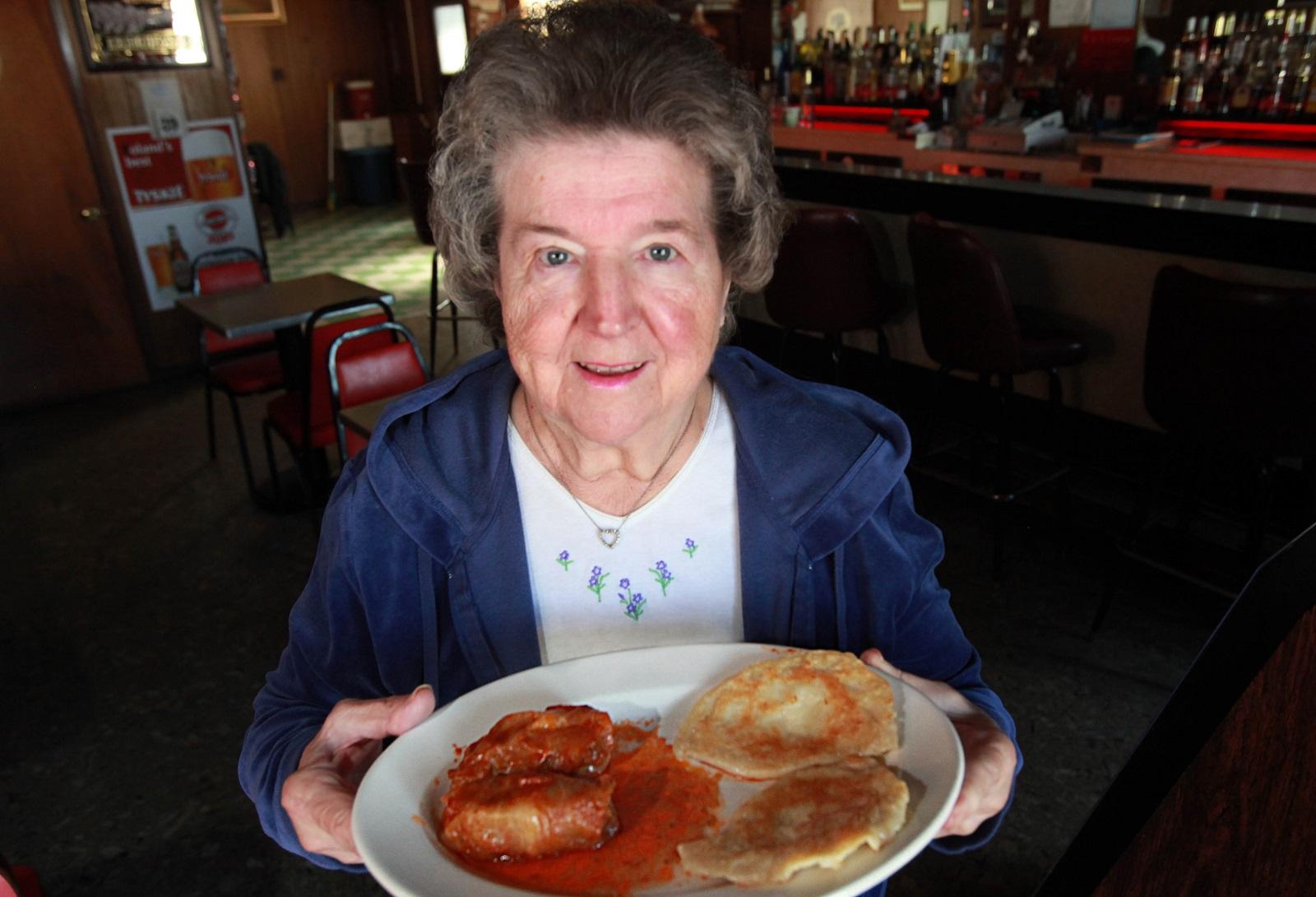 Lottie Pikuzinski, co-owner of R&L Lounge on Mills Street holds a plate of golabki and pierogi. (Sharon Cantillon/Buffalo News file photo)